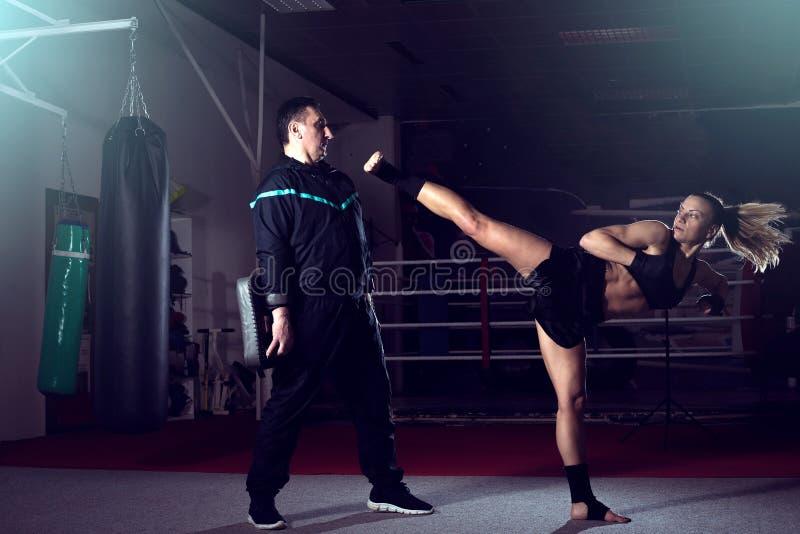 Flicka som tillbaka sparkar benet under kickboxing övning royaltyfri fotografi