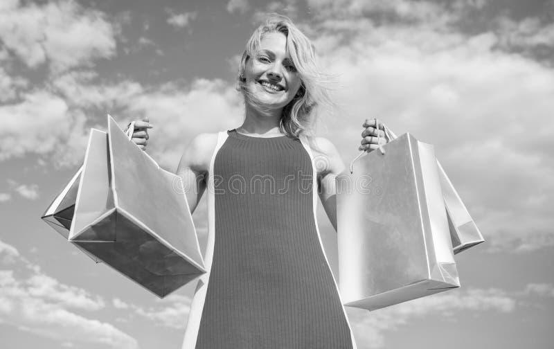 Flicka som tillfredsställs med köp Bär den röda klänningen för kvinnan bakgrund för blå himmel för gruppshoppingpåsar Shoppa den  arkivbild