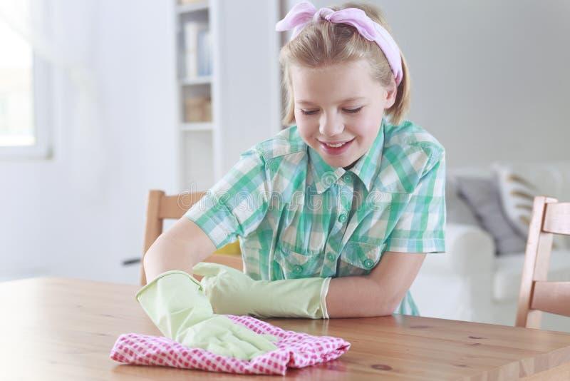 Flicka som torkar en tabell med lokalvårdtorkduken arkivfoto