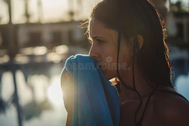 Flicka som torkar framsidan med handduken vid pölen royaltyfri bild