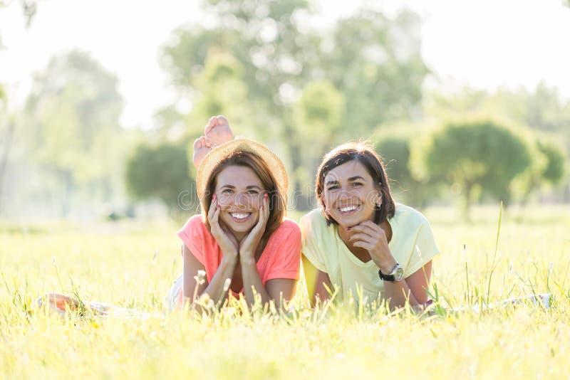 Flicka som två skrattar på gräs fotografering för bildbyråer