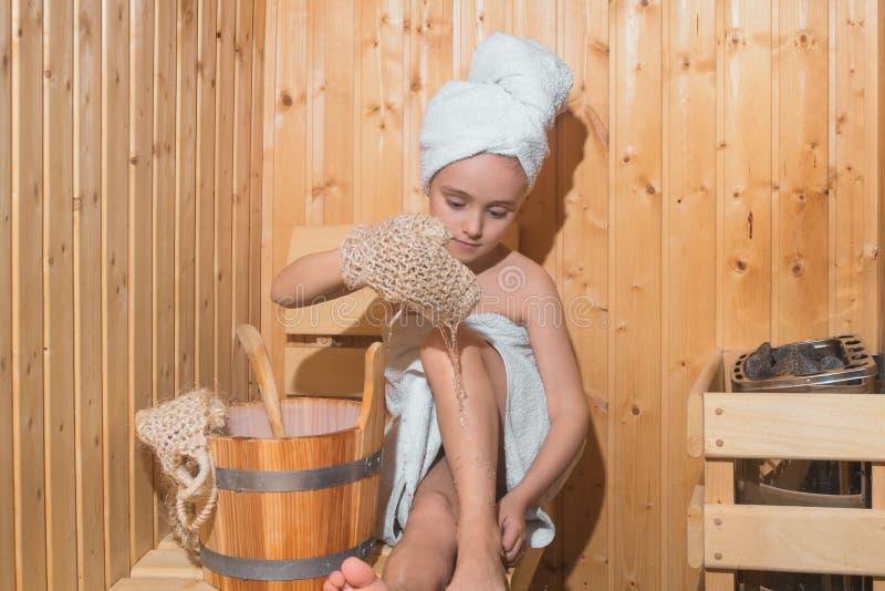 Flicka som tycker om ett avslappnande stag i bastun Ung flicka som kopplar av i bastu, flicka i en brunnsortbehandling i en tradi royaltyfria bilder