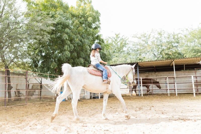 Flicka som tycker om hennes ritt på utbildad häst arkivfoto
