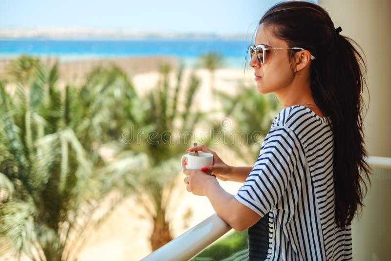 Flicka som tycker om koppen kaffe på en balkong royaltyfria bilder