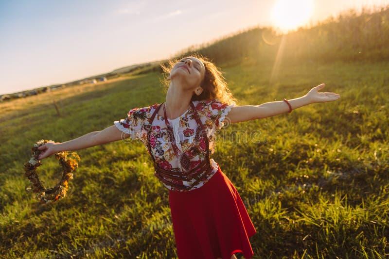 Flicka som tycker om naturen på fältet Flickan är den glade snurret med en krans av blommor i hennes händer royaltyfri bild