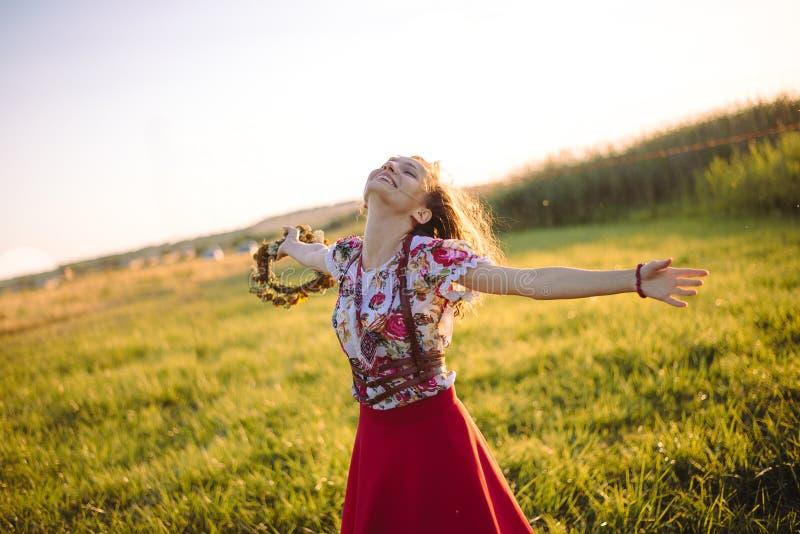 Flicka som tycker om naturen på fältet Flickan är den glade snurret med en krans av blommor i hennes händer royaltyfri foto