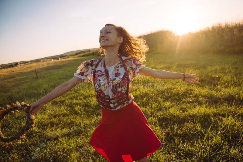 Flicka som tycker om naturen på fältet Flickan är den glade snurret med en krans av blommor i hennes händer arkivbilder