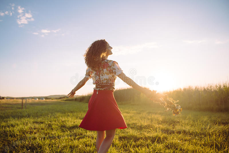 Flicka som tycker om naturen på fältet Flickan är den glade snurret med en krans av blommor i hennes händer royaltyfria foton