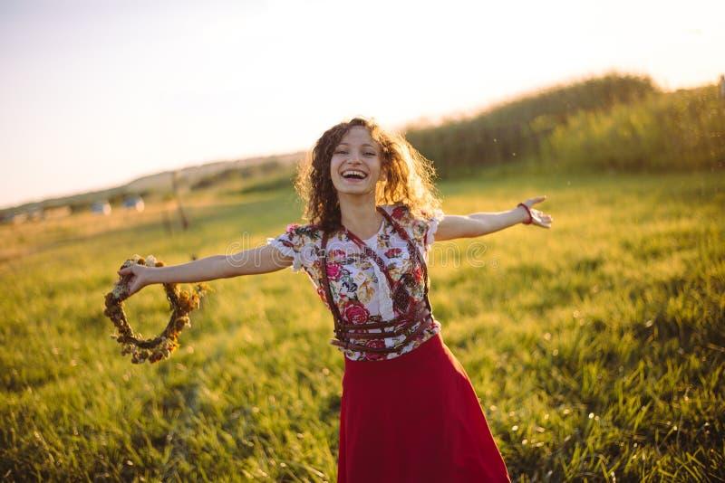 Flicka som tycker om naturen på fältet Flickan är den glade snurret med en krans av blommor i hennes händer fotografering för bildbyråer