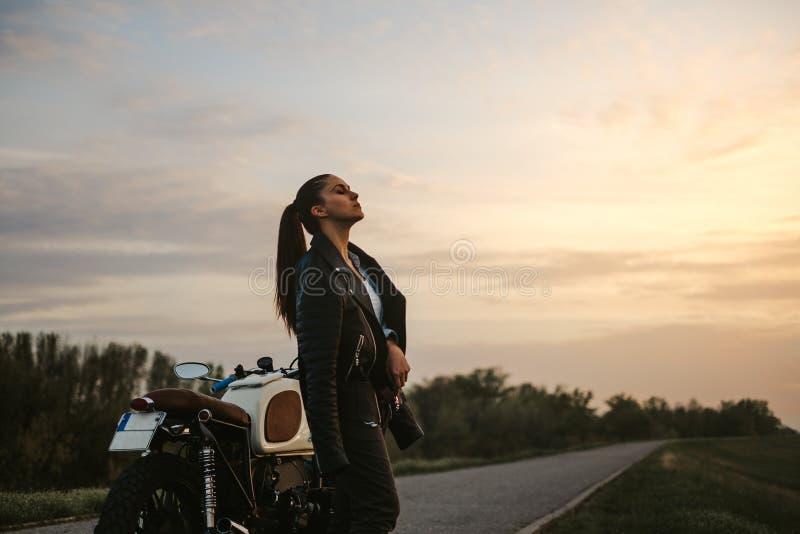 Flicka som tycker om solnedgång, medan stå vid motorcykeln royaltyfri bild