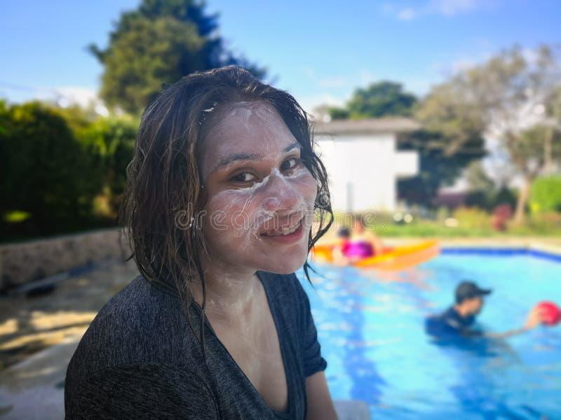 Flicka som tycker om sommarsemester i pölen Le framsidan som täckas i sunscreen royaltyfria foton