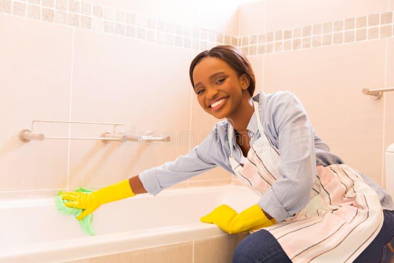 Flicka som upp gör ren badkaret royaltyfri bild