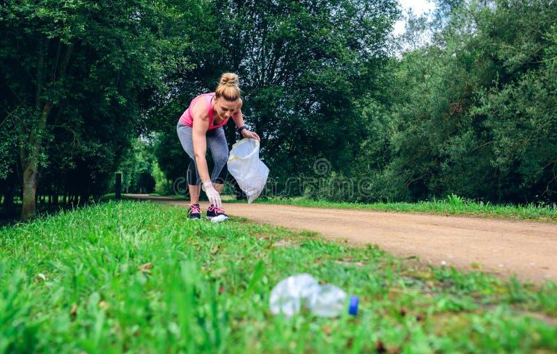 Flicka som upp väljer avfall som gör plogging arkivfoto