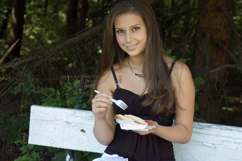 Flicka som utomhus äter lunch arkivbilder