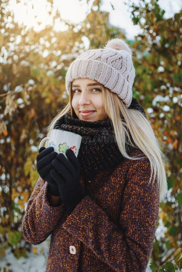Flicka som utomhus dricker varmt te i vinter royaltyfria foton