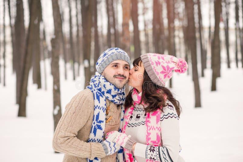 Flicka som utomhus kysser hennes pojkvän på kinden i vinter Bärande hemtrevlig varm kläder, stucken hatt och handskar Vinterdatum arkivbilder