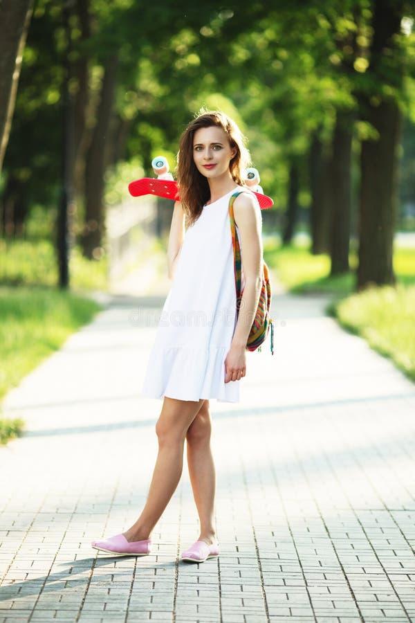 Flicka som utomhus rymmer ett plast- skridskobräde arkivfoto