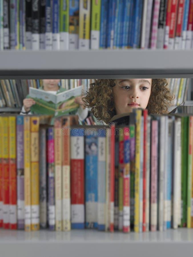 Flicka som väljer böcker från arkivbokhyllan royaltyfria bilder