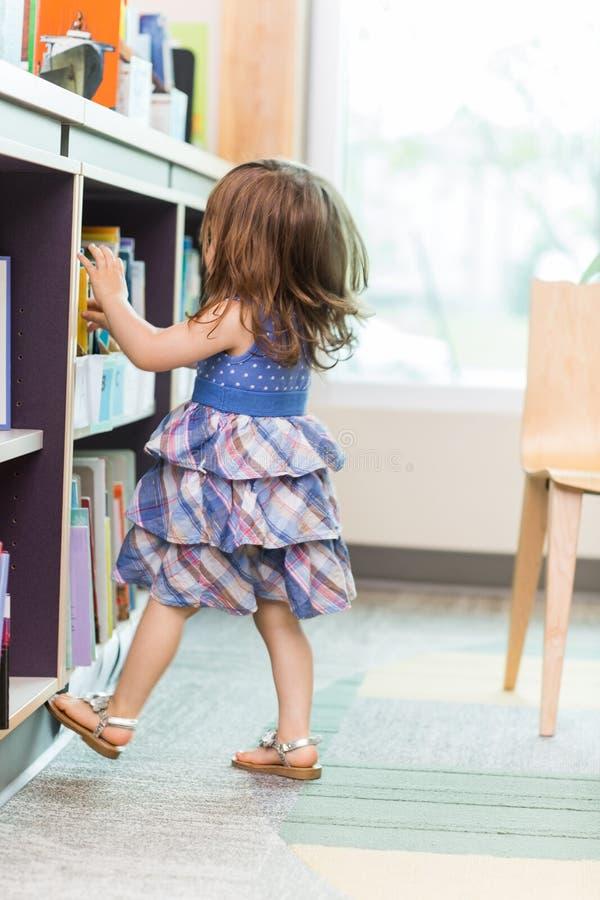 Flicka som väljer boken från skolaarkiv fotografering för bildbyråer