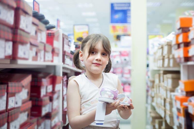 Flicka som väljer sommarskor i lager royaltyfria foton