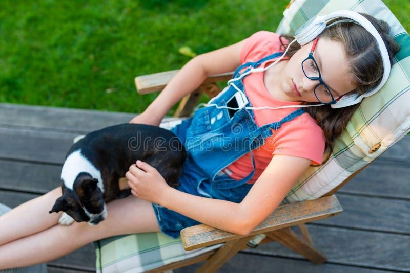 Flicka som vilar i trädgården med hennes hund och lyssnar till musik royaltyfria bilder