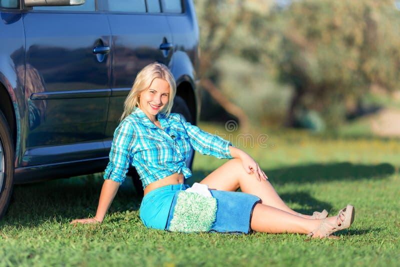Flicka som vilar nära bilen royaltyfri foto