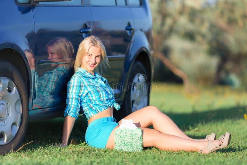 Flicka som vilar nära bilen arkivbild