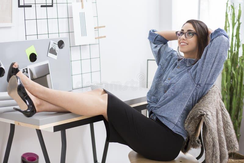 Flicka som vilar på arbete arkivbild