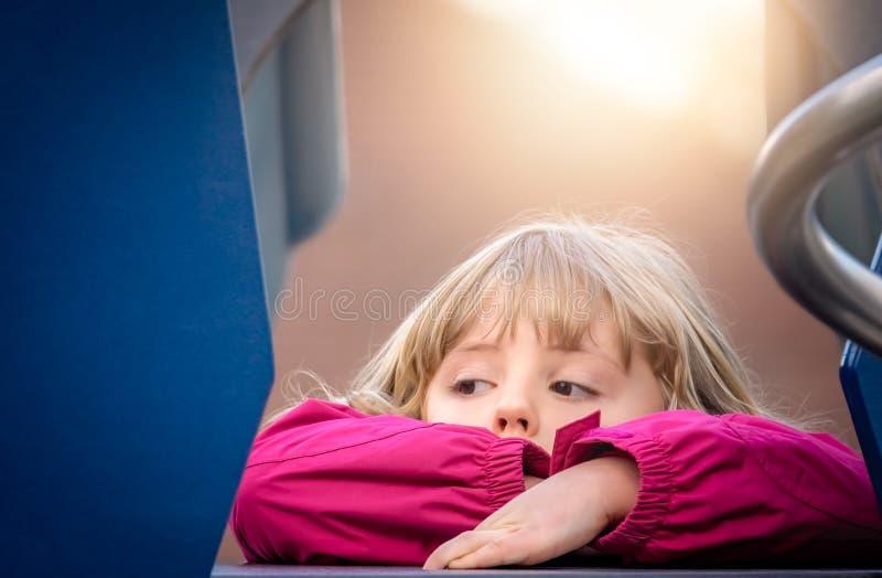 Flicka som vilar på en utomhus- glidbana royaltyfri fotografi
