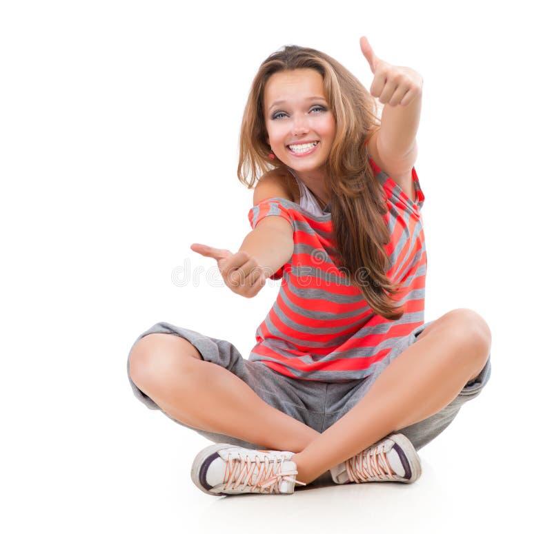 Flicka som visar upp tum arkivfoto