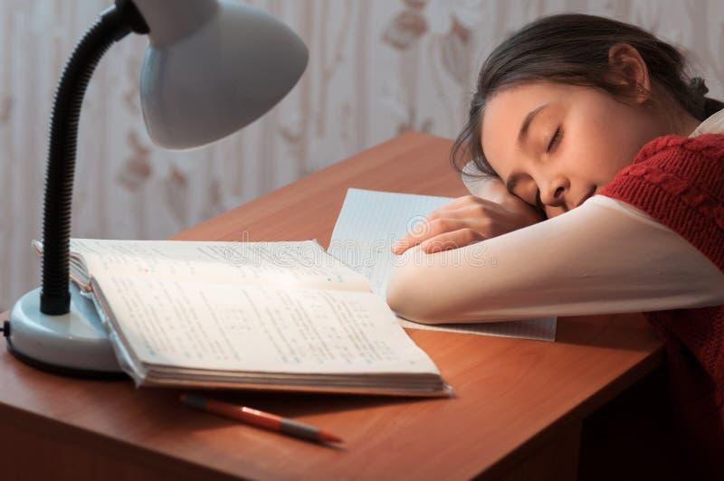 Flicka sovande på en bordlägga som gör läxa royaltyfri bild