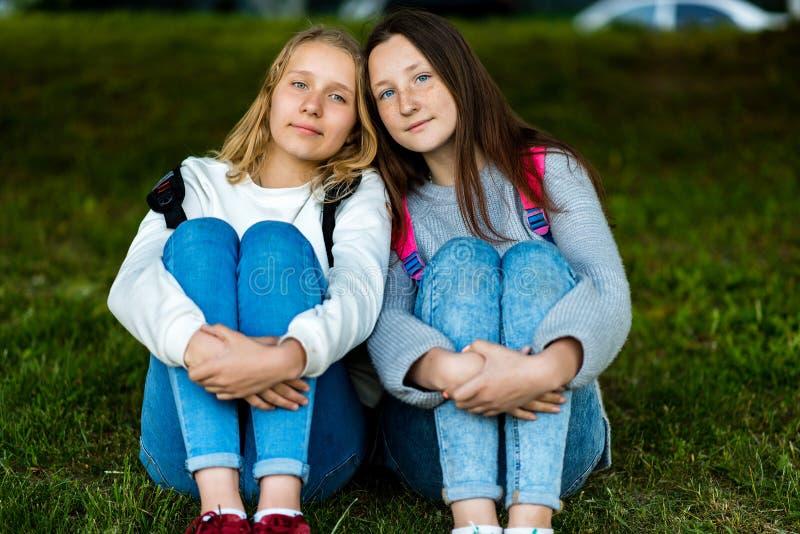 flicka tonårs- två Sommar i natur De sitter på gräs Meddela med de Att att posera på kameran bäst royaltyfri foto