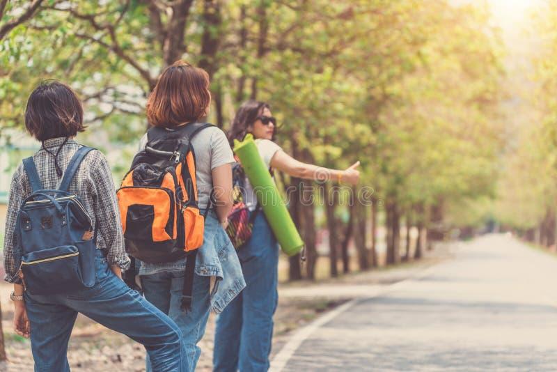 Flicka tre med hatten och ryggsäcken som liftar på vägen arkivbild