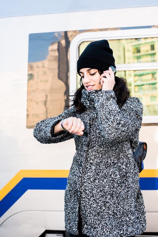 Flickaanseende bredvid ett drev som ser hennes klocka och talar på telefonen - nära övre royaltyfri foto