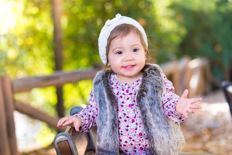 Flickaanseende för liten unge i en stol och le utomhus arkivfoto