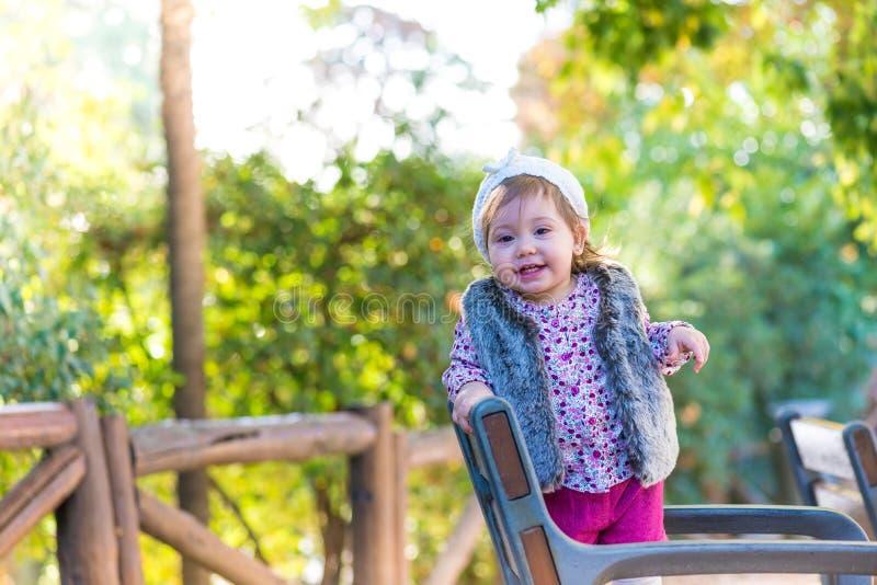 Flickaanseende för liten unge i en stol och le utomhus arkivbilder