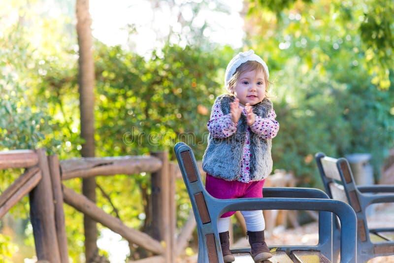 Flickaanseende för liten unge i en stol och le utomhus royaltyfri fotografi