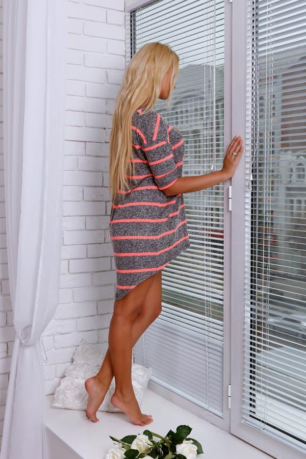 Flickaanseende nära ett stort fönster royaltyfri fotografi