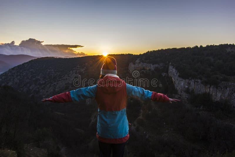 Flickaanseende på en klippa i berg på solnedgången arkivbilder