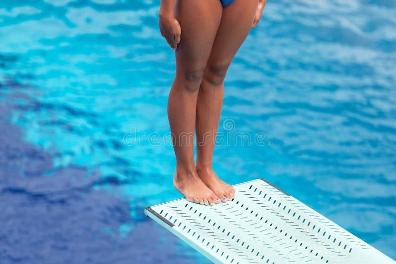 Flickaanseende på en språngbräda som förbereder sig att dyka in i en simbassäng arkivbild