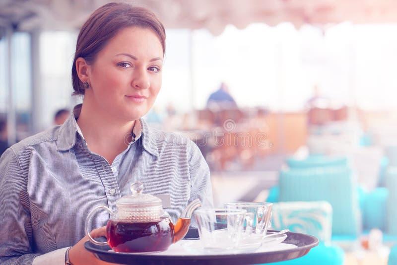 Flickaarbete som servitrins som rymmer ett magasin med te fotografering för bildbyråer