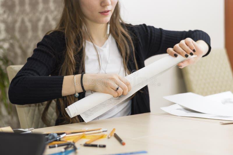 Flickaarkitekten drar ett plan, grafen, designen, geometriska former vid blyertspennan på det stora arket av papper på kontorsskr royaltyfri bild