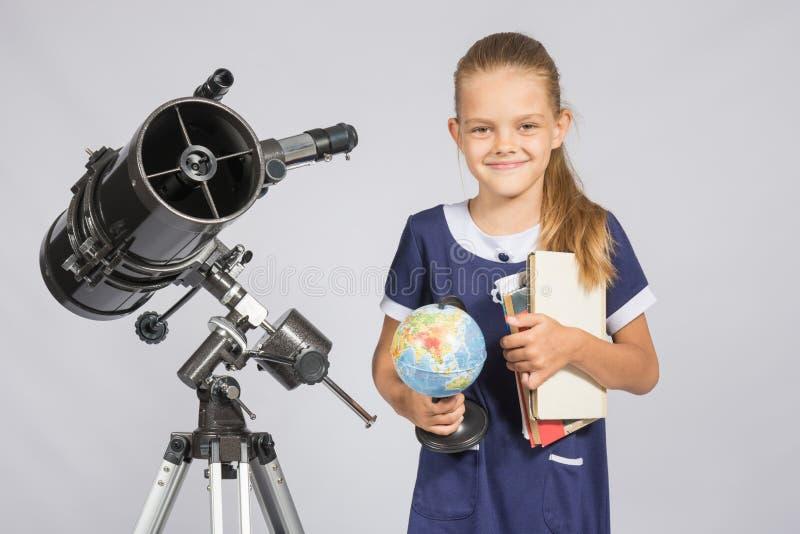 Flickaastronomen är ett teleskop med ett jordklot och bokar i händerna arkivfoton
