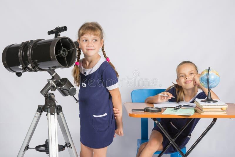 Flickaastronomen ser himlen, den annan flickan som lyckligt sitter på tabellen royaltyfria bilder