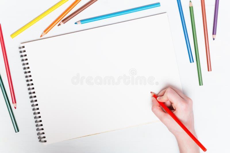 Flickaattraktioner med kulöra blyertspennor på papper arkivbilder