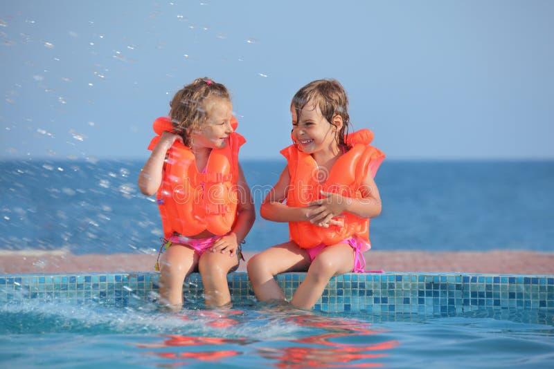 flickaavsatslifejackets pool att sitta två royaltyfri bild