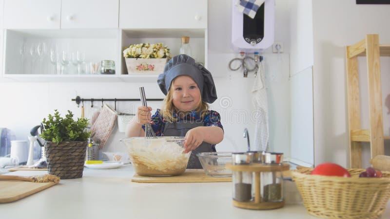 Flickabagaren blandar blandningen för kakor med en vifta royaltyfri bild