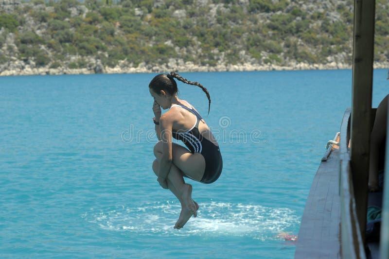 Flickabanhoppning in i vattnet fotografering för bildbyråer