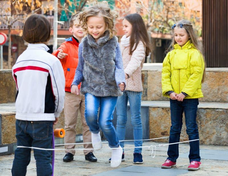 Flickabanhoppning medan lek för hopprep med vänner arkivfoton
