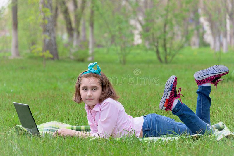 Flickabarn med bärbara datorn utomhus arkivfoton